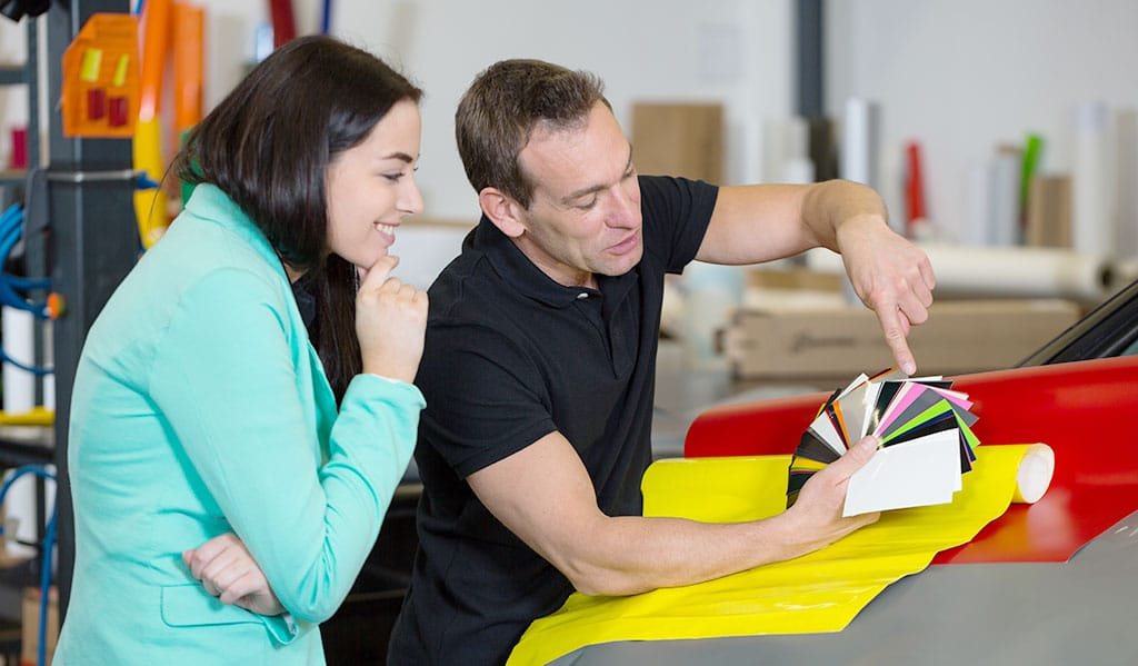 Car wrapping specialist consulting client about vinyl films