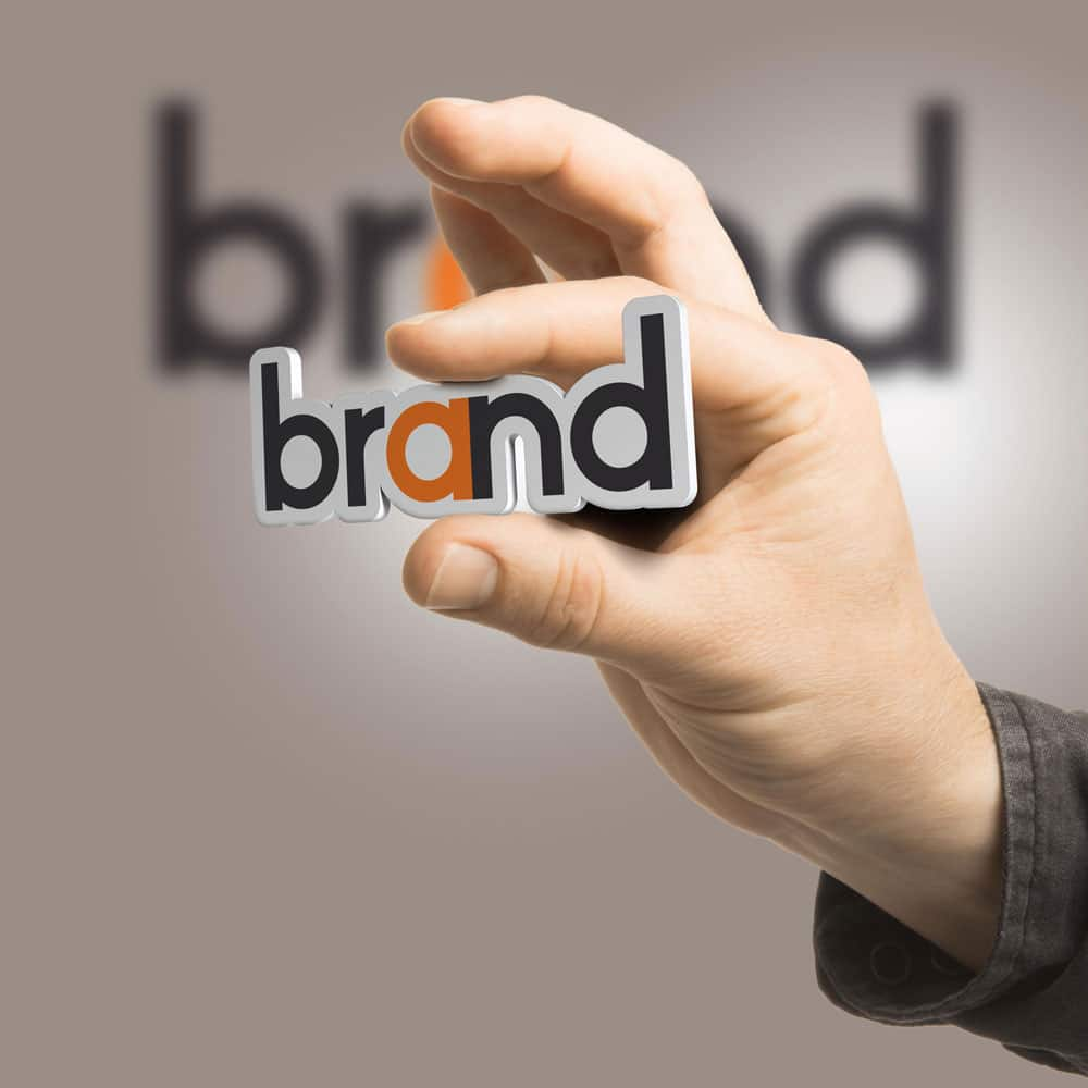 close up of hand holding the word brand