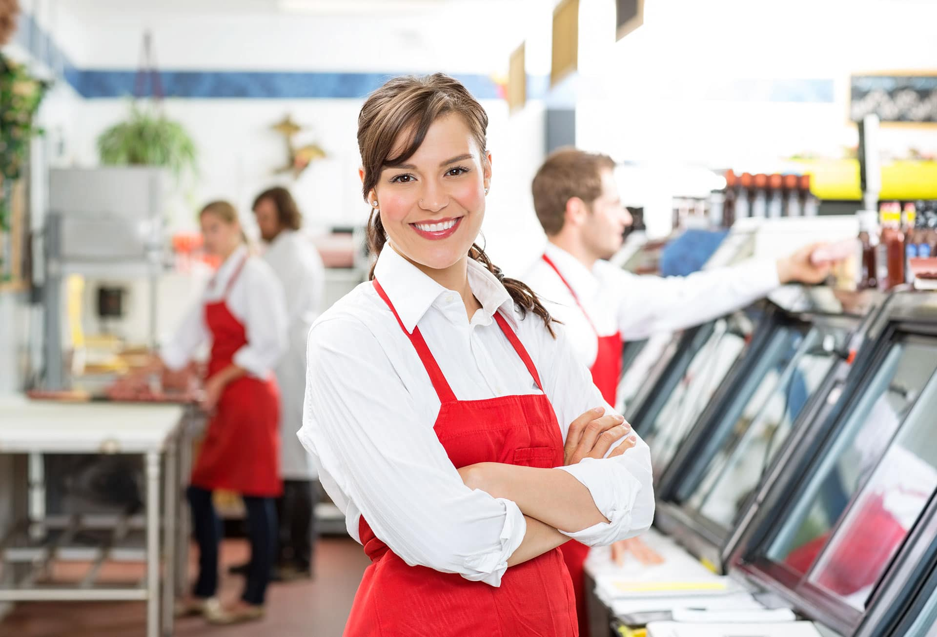 Confident female butcher standing arms crossed with colleagues in background